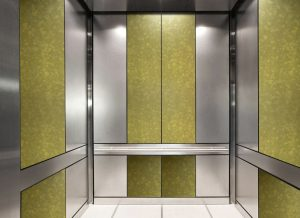 antique mirror in an elevator with bright gold decorative glass pattern