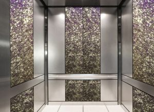 antique mirror in an elevator with purple decorative glass pattern