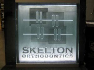 Skelton Orthodontics etched and carved glass sign